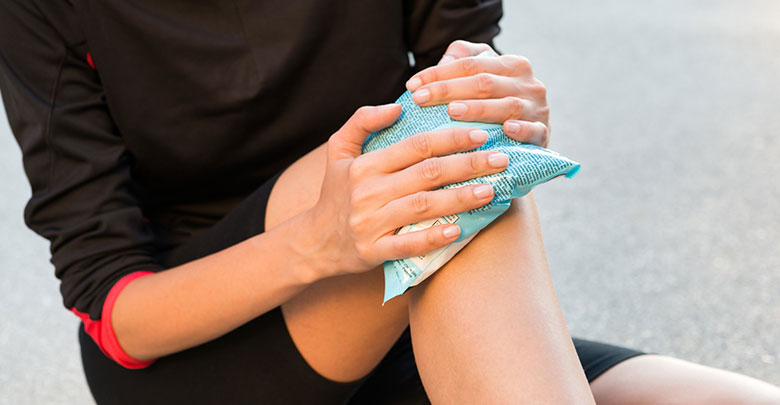 RICE stands for rest, ice, compression and elevation. A woman holds an ice pack on her painful knee