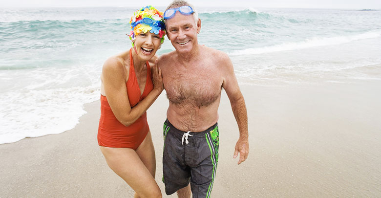 An older couple in fun swimsuits enjoy swimming in the ocean for their arthritis and pain.