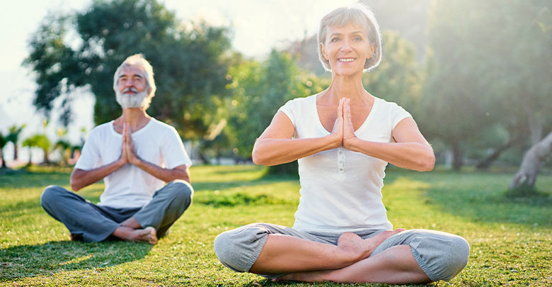 Yoga for arthritis is very beneficial. An older woman and man are sitting outdoors in nature and benefitting from yoga for their arthritis.