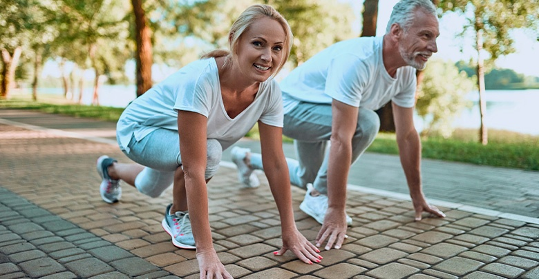 A middle aged couple enjoy the benefits of being able to exercise pain free outdoors in the sunshine.