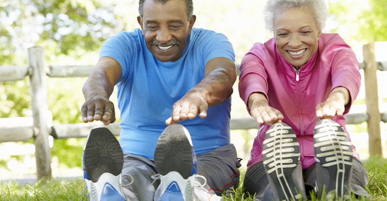 An older couple do their exercise for arthritis outside in the dappled sunshine.