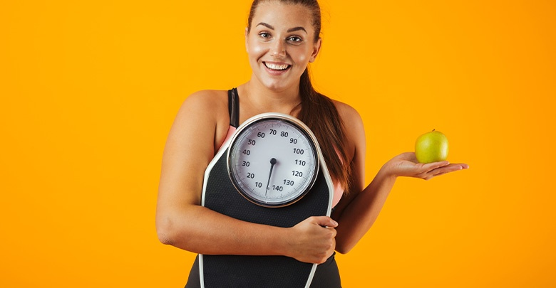 Attractive healthy young woman motivating you to lose weight, holding a scale and an apple.