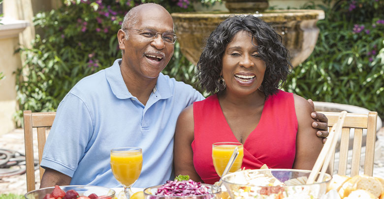 A laughing couple enjoy a healthy meal together outside.