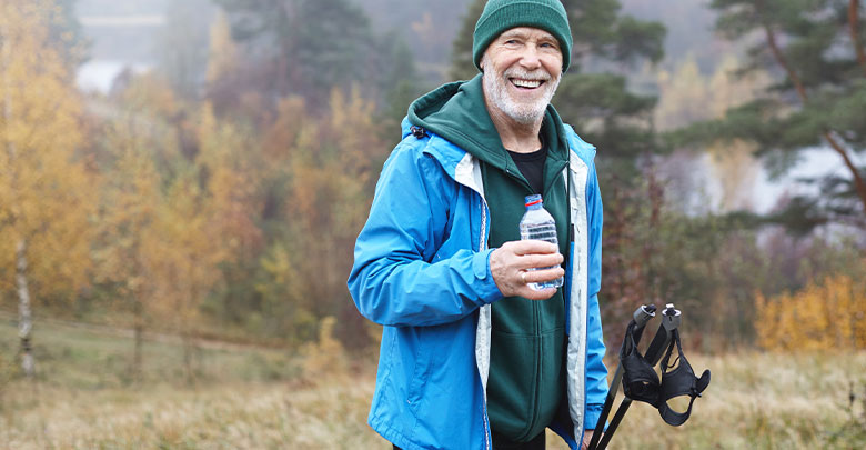 The best exercise to lose weight is walking - here an older man is hiking in the forest to get the benefits of exercising for weight loss and osteoarthritis.