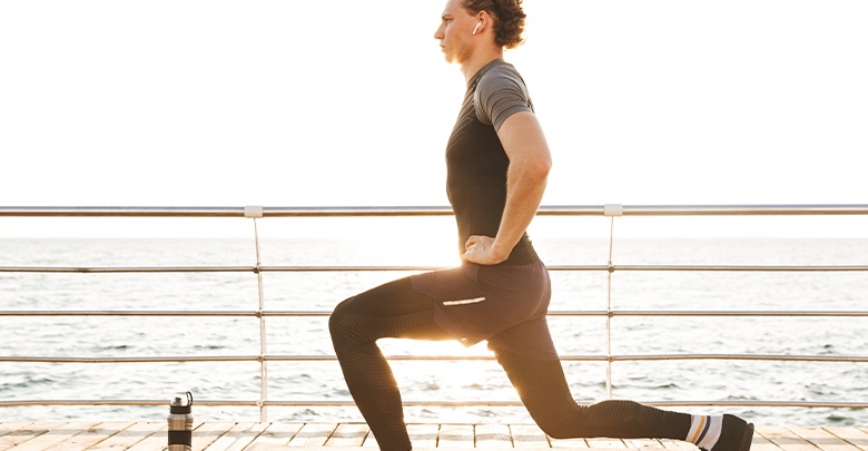 Young athletic man doing a lunge as a torn meniscus exercise on a seaside promenade