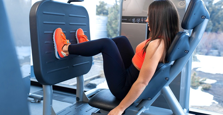 Young athletic woman doing a leg press as a torn meniscus exercise on a leg press machine at the gym